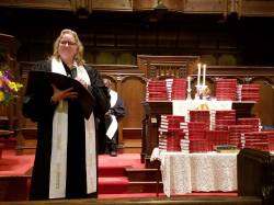 Rev. Brackett dedicates the new Bibles.